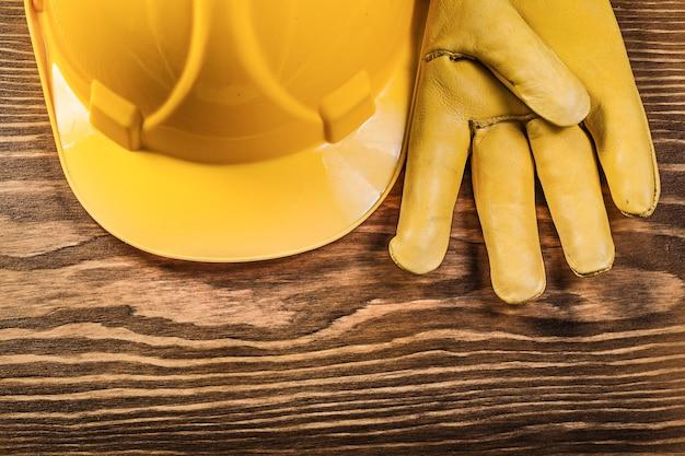 木の板の構造の概念のヘルメットを構築する革の安全手袋。