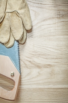 Leather safety gloves sharp handsaw on wooden board construction concept