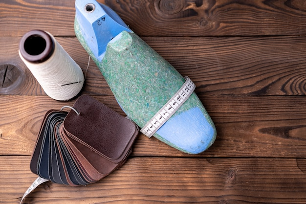靴と木製の靴の革のサンプルは、暗い木製のテーブルに残ります。デザイナー家具の服。靴メーカーのワークスペース。
