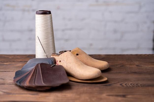 신발과 나무 신발의 가죽 샘플은 어두운 나무 테이블에 보관됩니다. 디자이너 가구 옷. 신발 메이커 작업 공간.