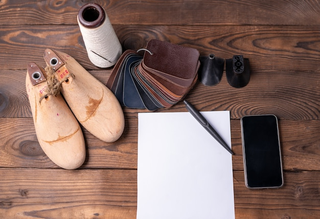 靴と木製の靴の革のサンプルは、メモ用の空の白い紙が付いた暗い木製のテーブルに残ります。デザイナーの家具の服。靴メーカーのワークスペース。