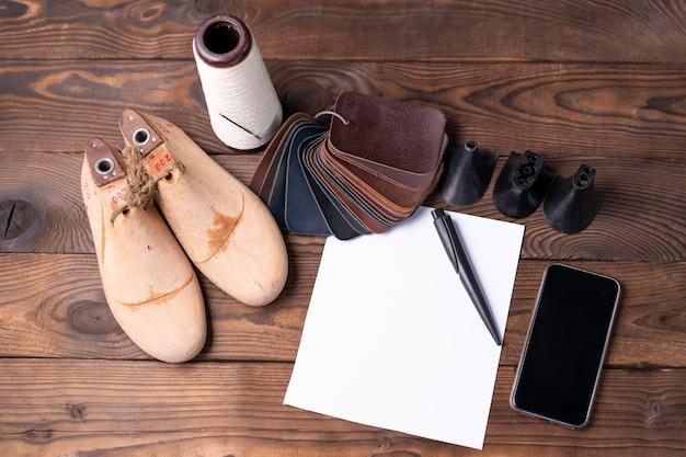 靴と木製の靴の革のサンプルは、メモ用の空の白い紙が付いた暗い木製のテーブルに最後にあります。デザイナー家具の服。靴メーカーのワークスペース。