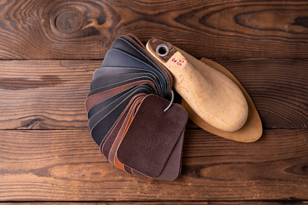 靴と木製の靴の革のサンプルは、暗い木製のテーブルに最後にあります