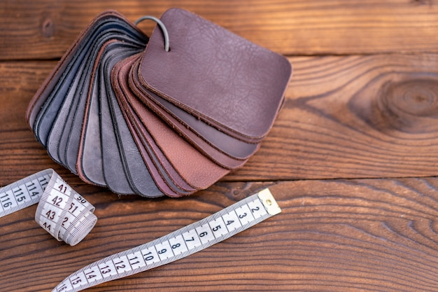 Leather samples and measuring tape on a wooden table