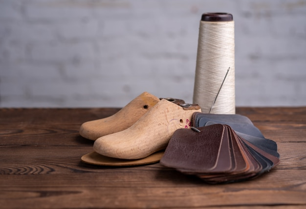 Leather samples for shoes and plastic shoe last on dark wooden table