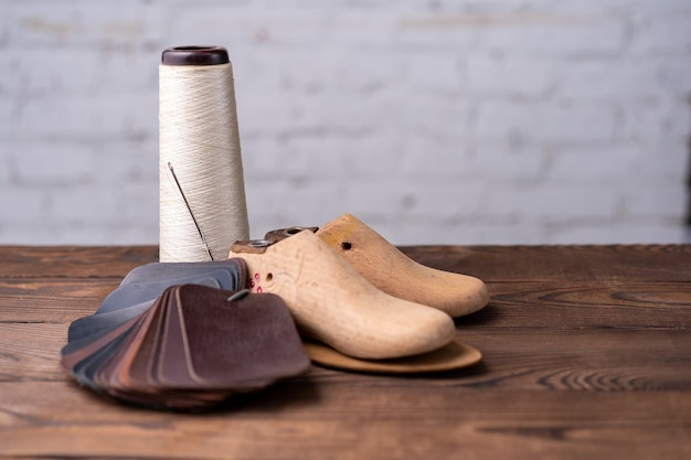 Leather samples for shoes and wooden shoe last on dark wooden table. designer furniture clothes. shoe maker workspace.