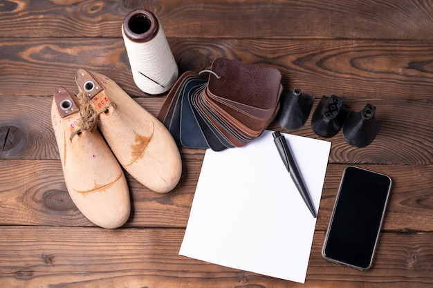 Leather samples for shoes and wooden shoe last on dark wooden table with empty white sheet of paper for notes.. designer furniture clothes. shoe maker workspace.