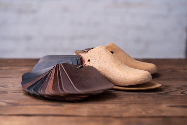 Leather samples for shoes and wooden shoe last on dark wooden table