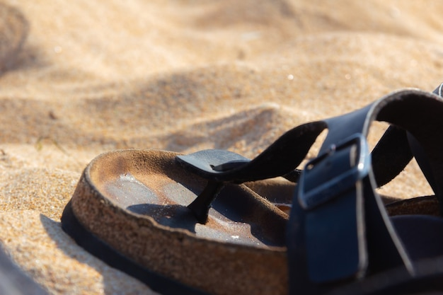 Leather sandal on the sand of the beach copy space