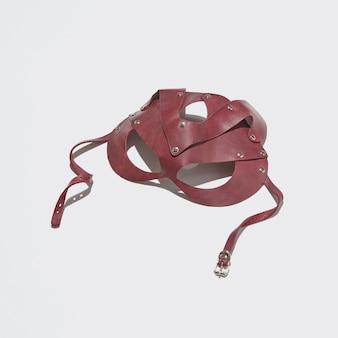 하드 그림자가있는 밝은 회색의 가죽 섹스 속성 빨간 고양이 마스크, 복사 공간. 섹스와 에로틱 한 게임 개념.