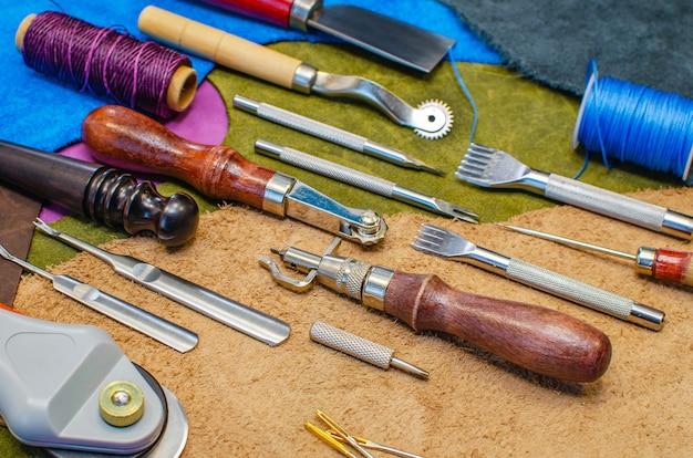 革靴職人のコンセプト。皮革事業では、ツールは色付きの皮革に広げられています。
