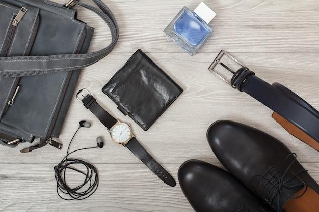 男性用レザーショルダーバッグ、ヘッドフォン、腕時計、財布、黒革の靴のケルンペアと灰色の木製の背景の男性用ベルト。メンズアクセサリー。上面図