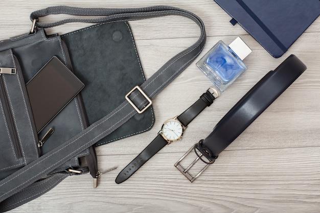 Кожаная мужская сумка через плечо с мобильным телефоном, наручными часами, мужским одеколоном, записной книжкой и мужским ремнем с серым деревянным фоном. аксессуары для мужчин. вид сверху