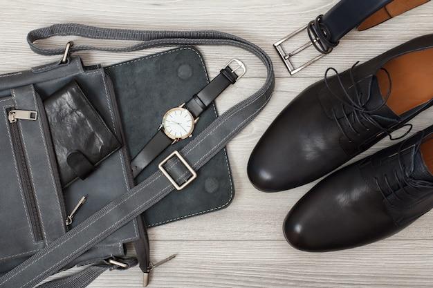 財布と腕時計が付いた男性用レザーショルダーバッグ、男性用ベルト、グレーの木製背景の黒い革製メンズシューズのペア。メンズアクセサリー。上面図