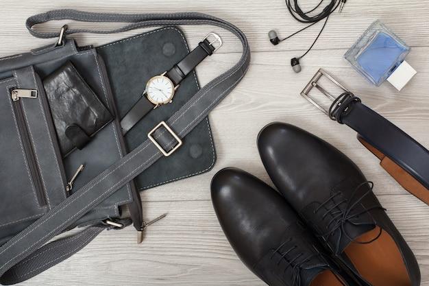 財布と腕時計が付いた男性用の革製ショルダーバッグ、黒い革の靴のペア、男性用のベルト、ケルン、灰色の木製の背景にヘッドフォン。メンズアクセサリー。上面図