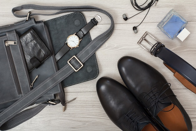 Leather shoulder bag for men with wallet and wristwatch on it, pairs of black leather shoes, belt for men, cologne and headphones on gray wooden background. men's accessories. top view