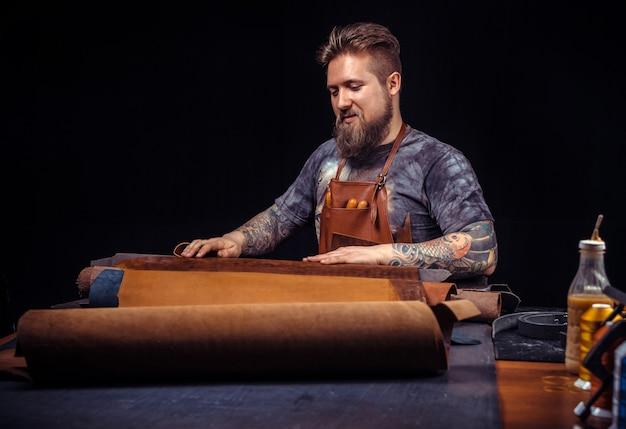 Кожевник производит изделия из кожи в кожевенной мастерской.