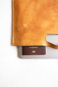 Leather suitcase with passport and laptop in concept of travel business.