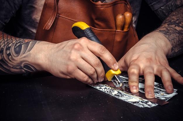 レザースタジオでの彼のビジネスに熱心なレザータナー。職人が机で新製品の革の形を切り抜く。