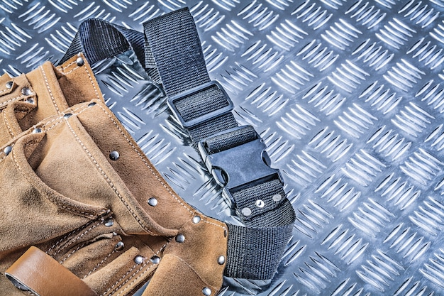 Leather tool belt on corrugated metal plate construction concept