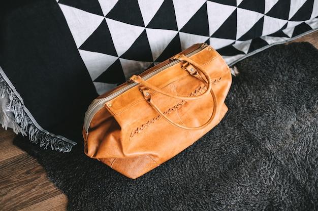 Кожаная дорожная сумка возле кровати в гостиной. подготовка к путешествию, концепция выходных.