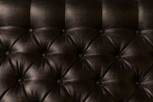 Leather upholstery on the sofa with light and shadow, close-up.
