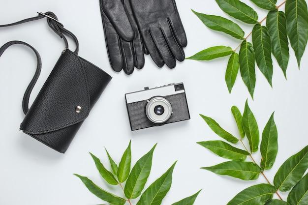 Кожаная поясная сумка, перчатки, ретро фотоаппарат на белом фоне с зелеными тропическими листьями. вид сверху