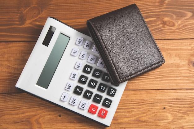 Кожаный кошелек и калькулятор на финансовом столе рашкет