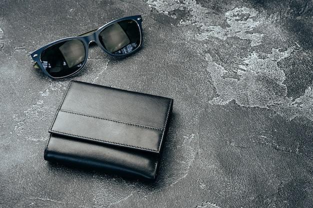 어두운 회색 배경에 가죽 지갑과 선글라스