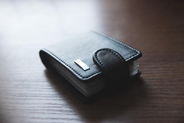 クレジットカード用の革の財布はテーブルの上に置かれます