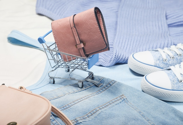 Leather wallet in a mini shopping trolley on the of things and accessories.