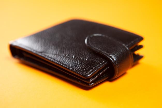 Leather wallet on orange surface