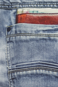 Кожаный кошелек с купюрами в кармане джинсов