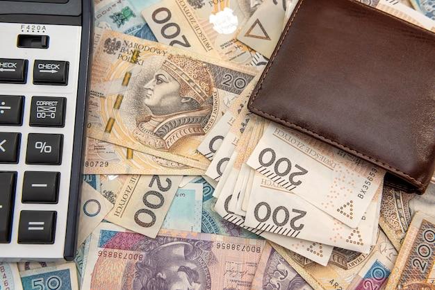 폴란드 즐로티 지폐에 계산기가 있는 가죽 지갑. 사업 배경