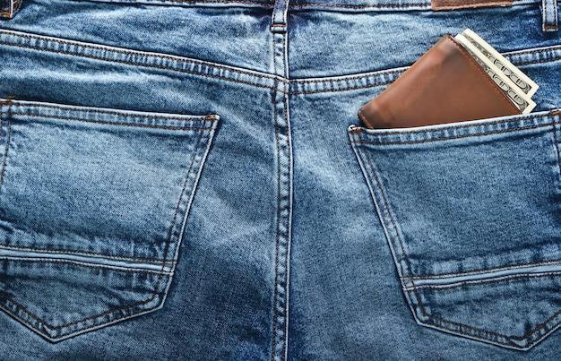 Кожаный кошелек со стодолларовыми купюрами в заднем кармане синих джинсов