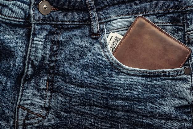 Кожаный кошелек со стодолларовыми купюрами в переднем кармане синих джинсов