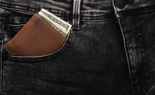 Кожаный кошелек со стодолларовыми купюрами в переднем кармане серых джинсов