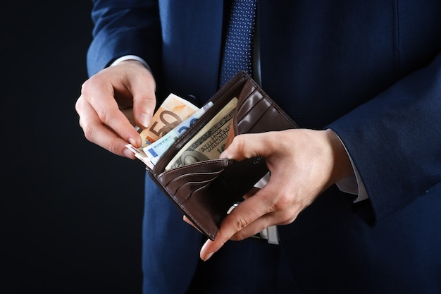 Leather wallet with money in male hands on dark background