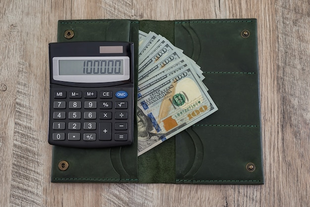 木製のテーブルに米ドルと電卓が付いた革の財布。