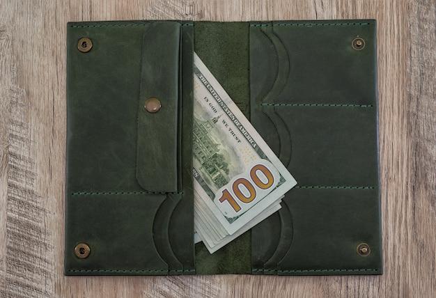 Кожаный кошелек с долларами сша на деревянном столе.
