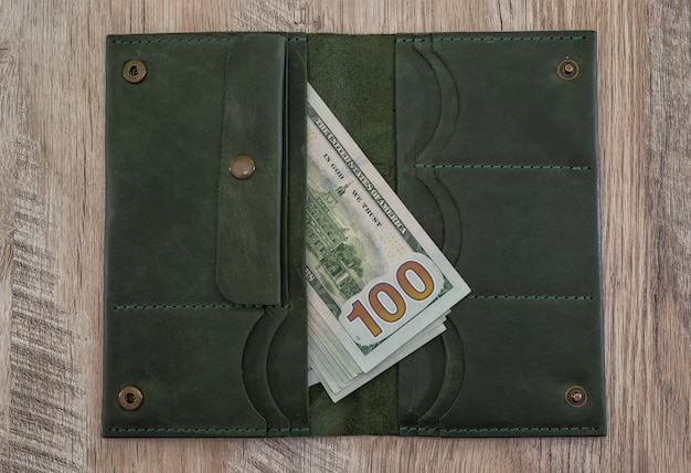 Leather wallet with us dollars on a wooden table.