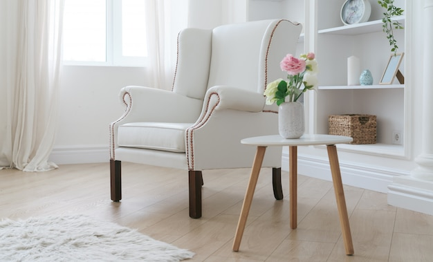 白い革張りのアームチェアと明るい部屋で花瓶とモダンな木製のテーブル
