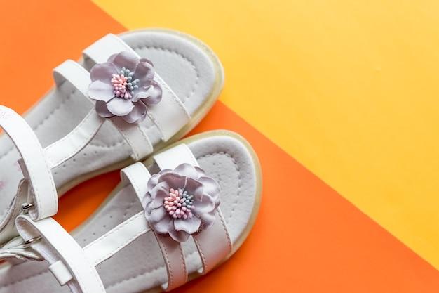 花の装飾が施された革の白い女の赤ちゃんの夏のサンダル。カラフルな背景に女の赤ちゃんの靴
