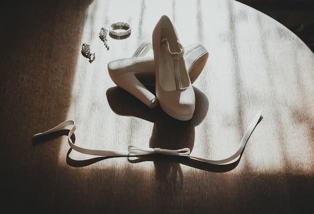 태양 광선에 나무 배경에 가죽 흰색 하이 힐 결혼식 신발.