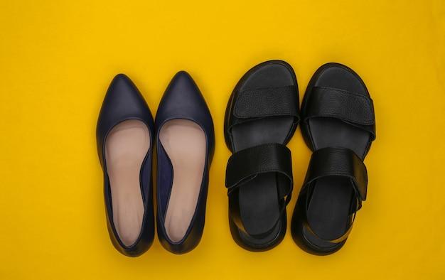 黄色の背景に革の女性のサンダルとハイヒールの靴。上面図。フラットレイ
