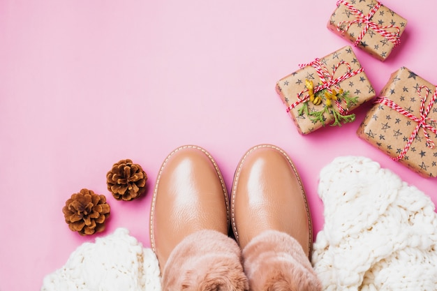Leather women's warm shoes with fur, white scarf and gifts boxes on light pink background. concept of the new year season. top view. cope space.