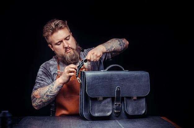 Кожевник работает с кожаными изделиями в своей мастерской.