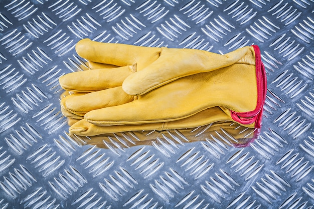 Leather working gloves on corrugated metal sheet construction concept