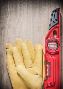 木の板の垂直バージョンの革作業用手袋赤建設レベル。