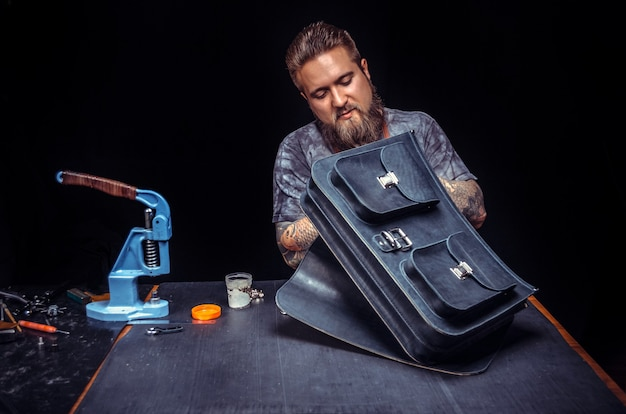 Leather workman creates a new leatherwork in the place of work.